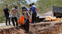 Petugas membawa jenazah korban gempa dan tsunami untuk dimakamkan massal di Palu, Sulawesi Tengah, Senin (1/10). (AP Photo/Tatan Syuflana)