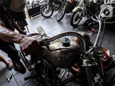 Pegawai bengkel motor custom menyelesaikan perakitan sepeda motor modifikasi di Classic Batavia Garage, Jakarta Selatan, Selasa (22/6/2021). Pandemi covid-19, bengkel Classic Batavia Garage kebanjiran jasa service dan modifikasi motor-motor sesuai dengan pesanan pelanggan. (Liputan6.com/Johan Tallo)