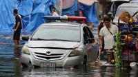 Sebuah mobil polisi terendam banjir yang disebabkan oleh hujan dari Topan Nock-Ten di kota Quezon, utara Manila, Filipina, (26/12). Topan super Nock-ten atau dikenal dengan Nina menerjang Filipina bertepatan saat Natal. (AP Photo / Aaron Favila)
