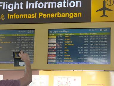 Calon penumpang mengambil gambar papan informasi penundaan penerbangan di Bandara Ngurah Rai, Bali, Jumat (29/6). Pihak pengelola menutup sementara aktivitas bandara maupun penerbangan karena gangguan abu vulkanis erupsi Gunung Agung. (AFP/GEDE ARDIASA)