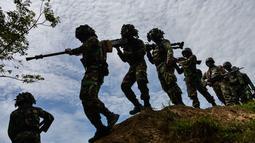 Sejumlah prajurit TNI dari batalyon infantri Raider 112 berjalan membawa senjata berat untuk latihan menembak di Mata Ie, Aceh Besar, Aceh, Selasa (11/6/2019). Latihan ini untuk menjaga keutuhan negara dari ancaman serta gangguan baik dari dalam maupun luar negeri. (AFP Photo/Chaideer Mahyuddin)