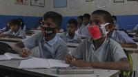 Sejumlah siswa mengenakan masker saat prose belajar mengajar di sebuah sekolah pemerintah di Hyderabad, India, Rabu (4/3/2020). Beberapa siswa memakai masker yang dibuat sendiri, dari kain maupun dari kertas. (AP Photo/Mahesh Kumar A.)