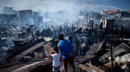Warga melihat rumah-rumah mereka hangus terbakar di sebuah daerah kumuh di Navotas, Manila (8/11). Dilaporkan sekitar 150 keluarga terkena dampak kebakaran tersebut. (AFP Photo/Noel Celis)