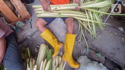 Pedagang membuat kulit ketupat dari anyaman daun kelapa muda (janur) di Pasar Pondok Labu, Jakarta Selatan, Kamis (30/7/2020). Pedagang musiman kulit ketupat yang sebagian datang dari Serang, Banten mulai ramai memadati kawasan Pasar Pondok Labu. (Liputan6.com/Fery Pradolo)