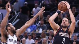 Pemain Housten Rockets, Ryan Anderson (3) bersiap menembak bola ke dalam ring dari kawalan Kawhi Leonard di gim kelima semifinal wilayah barat Playoffs NBA 2017 di AT&T Center, San Antonio, Texas (9/5). (Ronald Martinez/Getty Images/AFP)