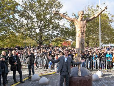 Bintang sepak bola Swedia Zlatan Ibrahimovic berpose dengan patung yang menyerupainya dekat Stadion Malmo, Malmo, Swedia, Selasa (8/10/2019). Ibrahimovic dikokohkan statusnya sebagai ikon Kota Malmo lewat sebuah patung. (Johan NILSSON/TT News Agency/AFP)