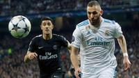 Pemain Real Madrid Karim Benzema dan pemain Paris Saint-Germain Yuri Berchiche mengejar bola pada leg pertama babak 16 besar Liga Champions di Stadion Santiago Bernabeu, Rabu (14/2). Sempat ketinggalan, Madrid akhirnya mengalahkan PSG 3-1. (AP/Paul White)