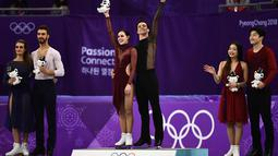 Pasangan Figure Skating Tessa Virtue dan Scott Moir (tengah) berada di podium usai meraih emas pada Olimpiade Musim Dingin Pyeongchang 2018 di Gangneung Ice Arena di Gangneung (20/2). (AFP Photo/Aris Messinis)