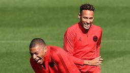 Pemain Paris Saint-Germain (PSG), Neymar (kanan) dan Kylian Mbappe (kiri) tertawa saat sesi latihan di Paris Barat, Prancis, Senin (17/9). PSG akan menghadapi Liverpool di Liga Champions pada 19 September 2018. (Anne-Christine POUJOULAT/AFP)