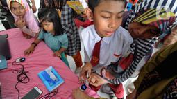 Murid-murid SLB mengikuti tes STIFIn di Sekolah Luar Biasa A Pembina Tingkat Nasional, Lebak Bulus, Jakarta, Selasa (17/12/2019). Tes tesebut dilakukan melalui menscan  ksepuluh ujung jari dengan mengambil waktu tidak lebih dari satu menit. (merdeka.com/Arie Basuki)