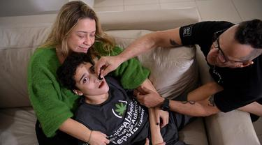 Gabriel Guerra (tengah) digendong ibunya Vanessa Opitz sedangkan ayahnya Ricardo Guerra memberinya ganja obat di Rio de Janeiro, Brasil, 20 September 2021. Ricardo memberi ganja obat kepada Gabriel dalam bentuk tetesan untuk membantu anaknya dari autisme berat dan cerebral palsy. (CARL DE SOUZA/AFP)