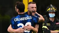 Hakan Calhanoglu merayakan gol yang dicetak bek Inter Milan, Milan Skriniar, ke gawang Genoa, Sabtu (21/8/2021) malam WIB. (MIGUEL MEDINA / AFP)
