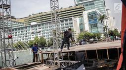 Pekerja menyelesaikan pembuatan panggung HUT ke-492 DKI di area Bundaran HI, Jakarta, Kamis (20/6/2019). Sejumlah artis Ibu Kota akan menghibur dalam peringatan HUT ke-492 DKI Jakarta. (Liputan6.com/Faizal Fanani)