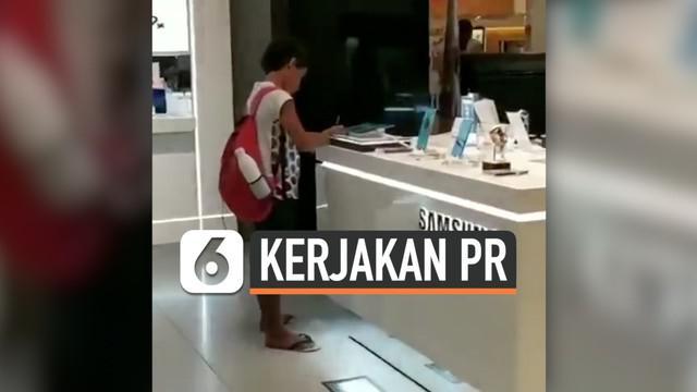 Seorang bocah mengerjakan tugas sekolahnya menggunakan perangkat display di gerai Samsung. Ini dilakukannya karena tak memiliki gadget dan juga internet.