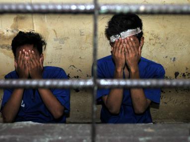 Dua pelaku penjambretan menutup wajahnya saat berada di dalam sel, Polsek Johar Baru, Jakarta, Senin (25/1/2016). Pelaku tertangkap dan dihakimi warga saat menjambret sebuah ponsel. (Liputan6.com/Yoppy Renato)