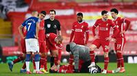 Kapten Liverpool, Jordan Henderson, harus mendapatkan perawatan hingga akhirnya harus meninggalkan lapangan lebih cepat saat memperkuat The Reds menghadapi Everton pada pekan ke-25 Premier League, Minggu (21/2/2021) dini hari WIB. Liverpool kalah 0-2 dalam laga ini. (LAURENCE GRIFFITHS / POOL / AFP)