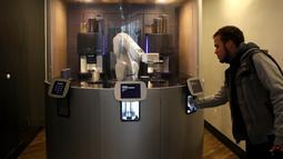 Seorang pelanggan mengambil kopi yang dibuat oleh robot barista di Cafe X, San Francisco, California, AS, Selasa (12/2). Cafe X memiliki robot yang mampu membuat tiga gelas kopi dalam 40 detik. (Justin Sullivan/Getty Images/AFP)