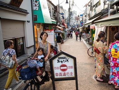 Seorang wanita mengendarai sepeda membawa anak-anaknya melihat ke arah sejumlah wanita yang mengenakan pakaian tradisional yang berbelanja di jalan Yanaka ginza di pusat Tokyo (30/9/2019). Wilayah Yanaka di ibukota Jepang dikenal sebagai salah satu yang paling kuno dan unik. (AFP Photo/Odd Andersen)