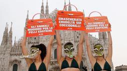 Aktivis PETA (People for the Ethical Treatment of Animals) menunjukkan poster berbentuk tas berisi kecaman mereka untuk para brand fashion yang menggunakan kulit hewan, Italia, Selasa (21/2). (AP Photo/Antonio Calanni)
