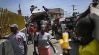 Penduduk setempat memuat kasur di atap bus di pasar Petion-Ville di Port-au-Prince, empat hari setelah pembunuhan Presiden Haiti Jovenel Moise, Minggu (11/7/2021). Moïse tewas dibunuh dalam serangan di kediaman pribadinya, pada Rabu 7 Juli 2021 dini hari. (AP Photo/Matias Delacroix)