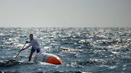 Nicolas bersemangat mendayung papan selancar saat berlatih di perairan lepas Martigues, Perancis, Selasa (15/3). Dengan menggunakan papan selancar dayung yang sudah dimodifikasi Jarossay akan menyeberangi Samudera Atlantik. (AFP/BORIS HORVAT)