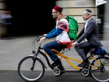 Seorang Muslim dan pria Yahudi mengayuh sepeda dengan berboncengan sebagai kampanye lintas agama melintasi Ibu Kota Jerman, Berlin, 24 Juni 2018. Aksi lintas iman ini untuk melawan kebencian atas nama agama di negara tersebut. (AP Photo/Markus Schreiber)