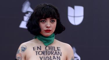 Penyanyi Chile Mon Laferte berpose di karpet merah Latin Grammy Awards 2019, MGM Grand Garden Arena, Las Vegas, Amerika Serikat, Kamis (14/11/2019). Mon menuliskan kalimat 'Di Chile mereka menyiksa, memperkosa, dan membunuh' di tubuhnya. (Bridget BENNETT/AFP)
