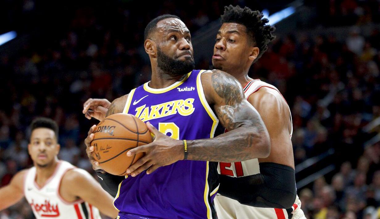 Pebasket Los Angeles Lakers, LeBron James, berusaha melewati pebasket Portland Trail Blazers, Hassan Whiteside, di Moda Center, Sabtu 928/12). LA Lakers menang 128-120 atas Portland Trail Blazers. (AP/Craig Mitchelldyer)