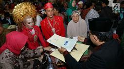Sejumlah pasangan mengikuti nikah massal di malam pergantian tahun di Jalan MH Thamrin, Jakarta, Minggu (31/12). Sedikitnya 100 penghulu telah disiapkan Pemprov DKI Jakarta.  (Liputan6.com/Angga Yuniar)