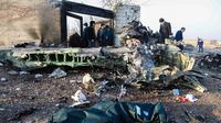 Orang-orang berdiri di antara puing-puing setelah pesawat Boeing 737 jatuh di dekat Bandara Internasional, Teheran, Iran, Rabu (8/1/2020). Seluruh penumpang pesawat maskapai Ukraina yang membawa 176 orang termasuk kru tersebut dilaporkan tewas. (ROHHOLLAH VADATI / ISNA / AFP)