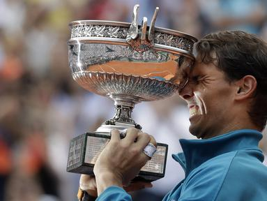 Rafael Nadal mengangkat trofi Prancis Terbuka 2018 setelah mengalahkan petenis Austria, Dominic Thiem pada final di Roland Garros stadium, Paris, (10/6/2018). Nadal menang tiga set 6-4, 6-3, 6-2. (AP/Alessandra Tarantino)