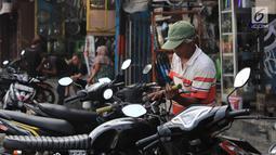 Mekanik mengecek motor pelanggan di sebuah bengkel di Otista, Jakarta, Minggu (10/6). Calon pemudik motor mulai memenuhi bengkel guna menyervis atau mengganti suku cadang kendaraan sebelum digunakan untuk mudik Lebaran. (Liputan6.com/Angga Yuniar)
