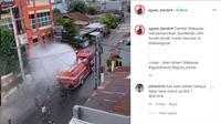 Petugas sedang melakukan penyemprotan disinfektan di Jalan Ablam, Makassar. (@agoez_bandz4)