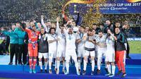 Para pemain Real Madrid melakukan selebrasi mengangkat trofi Piala Dunia Antarklub 2017 di stadion Zayed Sports City di Abu Dhabi, Uni Emirat Arab, (16/12). Madrid sukses mengalahkan Gremio 1-0 berkat gol Cristiano Ronaldo. (AP Photo / Hassan Ammar)