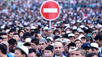 Rambu lalu lintas terlihat di antara ratusan muslim Rusia yang tengah melaksanakan salat Idul Fitri di luar masjid di pusat kota Moskow, Selasa (5/7). Perayaan Idul Fitri 1437 H di Rusia jatuh pada hari ini. (Kirill KUDRYAVTSEV/AFP)