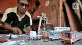 Iskandar (52) saat menyelesaikan pembuatan miniatur kereta api di kawasan Manggarai, Jakarta, Kamis (21/11/2019). Sudah 6 tahun bapak dari 2 anak ini menekuni profesi sebagai pembuat miniatur kereta api berbagai jenis, mulai dari KRL, kereta jarak jauh, hingga MRT. (merdeka.com/Iqbal S. Nugroho)