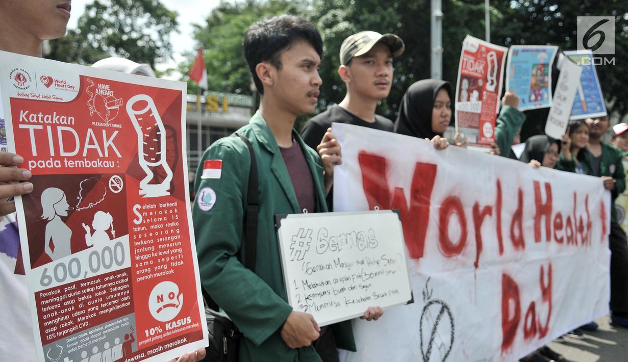 Mahasiswa Universitas Muhammadiyah Prof. Dr. Hamka membentangkan spanduk saat menggelar kampanye bahaya merokok di car free day (CFD), Jakarta, Minggu (8/4). Kampanye digelar untuk memperingati Hari Kesehatan Dunia. (Merdeka.com/Iqbal Nugroho)
