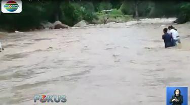 Warga terpaksa menggotong motor menyeberangi sungai karena tidak adanya jembatan di sungai tersebut.