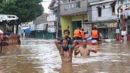 Warga melintasi banjir di perumahan Ciledug Indah, Tangerang, Rabu (1/1/2020). Banjir setinggi dada orang dewasa terjadi akibat meluapnya kali angke. (Liputan6.com/Angga Yuniar)