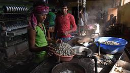 Pekerja pabrik merebus kepompong murbei di pabrik sutra tertua di Srinagar, Kashmir, India, Senin (30/7). (Tauseef MUSTAFA/AFP)