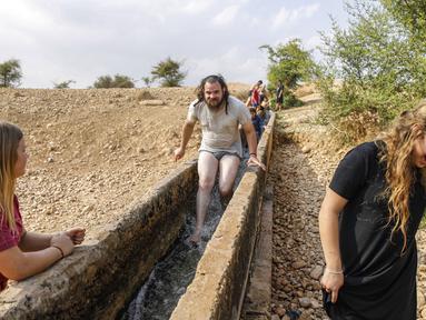 Warga Israel bermain air di sebuah kanal kecil di Desa Al-Auja selama perayaan keagamaan Yahudi dalam Festival Sukkot di Tepi Barat (17/10/2019). Festival Yahudi di Sukkot memperingati pengembaraan padang pasir alkitabiah orang Israel setelah eksodus mereka dari Mesir. (AFP Photo/Menahem Kahana)