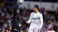 Kiper Athletic Bilbao, Kepa Arrizabalaga Revuelta berebut bola dengan pemain Real Madrid, Cristiano Ronaldo pada pekan ke-33 La Liga di Santiago Bernabeu, Rabu (18/4). Menjamu Athletic Bilbao, Real Madrid harus puas bermain imbang 1-1 (JAVIER SORIANO/AFP)