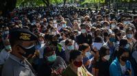 Polisi melakukan pengamanan saat warga menunggu dalam antrean untuk mendaftar vaksin virus corona COVID-19 AstraZeneca di Denpasar, Bali, Sabtu (26/6/2021). Ratusan warga terlihat antusias mengikuti vaksinasi massal ini. (SONY TUMBELAKA/AFP)
