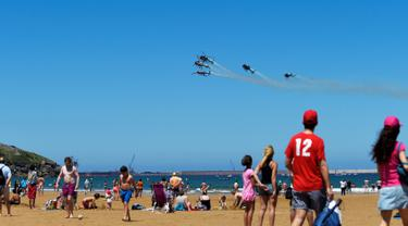 Para pengunjung pantai saat menyaksikan aksi tim aerobatik Angkatan Udara Spanyol, Patrulla Aspa yang bermanuver menggunakan helikopter di San Lorenzo, Gijon, Spanyol, Minggu (24/7). (REUTERS/Eloy Alonso)