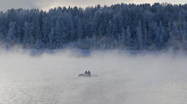 Tampak dua orang mendayung perahu di sepanjang Sungai Yenisei ditengah kabut dingin di Taiga luar kota Siberia Krasnoyarsk, Rusia, Selasa (17/11/2015). Suhu udara minus hingga 20 derajat Celsius. (REUTERS/Ilya Naymushin)