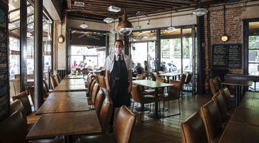 Pelayan Restoran Le Jaures Sami El Ouardi (32) berfoto dalam restoran sehari sebelum pembukaan kembali restoran dalam ruangan secara nasional di Paris, Prancis, Selasa (8/6/2021). Prancis akan membuka restoran dalam ruangan pada 9 Juni 2021. (AP Photo/Lewis Joly)