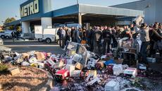 Minuman anggur ditumpahkan saat aksi protes di sebuah hypermarket di Nimes, Perancis, Kamis (20/4). Pedagang minuman Perancis marah karena harga minuman anggur dari Spanyol terlampau murah. (AP Photo / Arnold Jerocki)