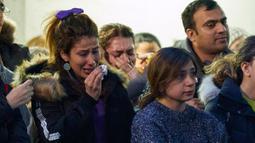 Seorang perempuan menangis saat kebaktian untuk empat mahasiswa pascasarjana korban pesawat 737-800 Ukraina yang jatuh di Iran, di salah satu universitas di Ontario, Kanada, Rabu (8/1/2020). Pesawat yang membawa 176 orang itu jatuh setelah lepas landas dari bandara utama Teheran. (Geoff Robins/AFP)