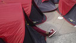 Kaki seorang imigran digambarkan di sebuah kamp darurat yang didirikan di luar balai kota Paris, pada Jumat (25/6/2021). Lebih dari 300 migran mendirikan sekitar 200 tenda di luar balai kota untuk menarik perhatian terhadap kondisi mereka dan menuntut akomodasi. (AP Photo/Lewis Joly)