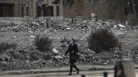 Seorang perempuan mengenakan masker berjalan melewati puing-puing di kota Raqa, bekas ibu kota ISIS, di Suriah utara pada 20 Desember 2020. Raqqa menjadi saksi terusirnya anggota kelompok ekstremis oleh Pasukan Demokratik Suriah pada Oktober 2017 lalu. (Photo by Delil SOULEIMAN / AFP)